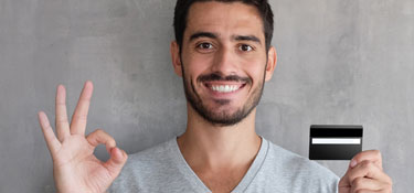 Man holding up credit card with an ok hand gesture.