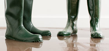 Couple in wellington boots on flooded floor