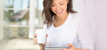 Woman smiling while looking at tablet.