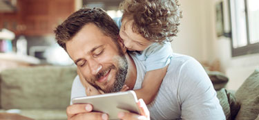 Father and son using phone together