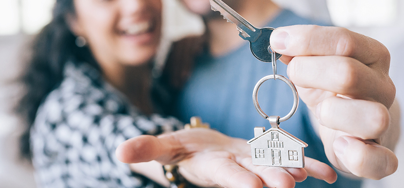 couple holding key to house