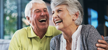 Senior couple laughing on couch