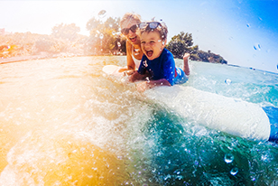 woman and child in water on surfboard